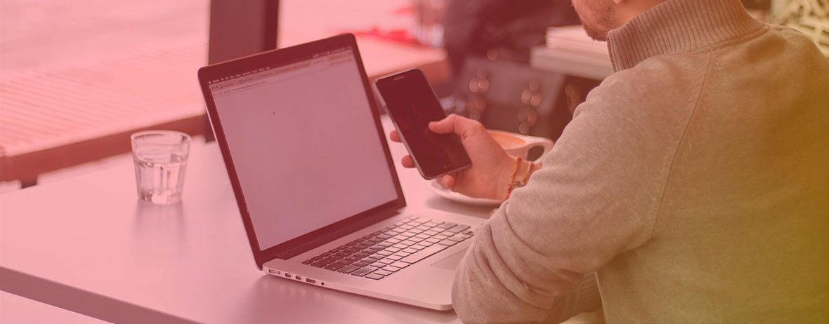 Man sitting at a café table, looking at phone and laptop screens